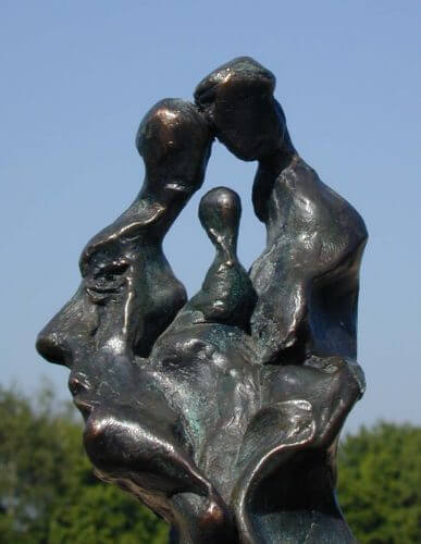 Tête-de-famille. The original bronze maquette. The photo shows the left side of a head, and the outline of an eyebrow, an eye, the nose, lips and chin are clear. The top of the head is formed by three figures implying father, mother and child.