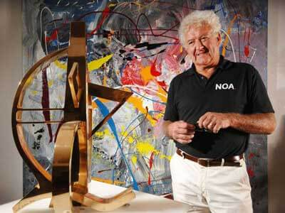 contemporary British sculptor, Neil Lawson Baker, standing in front of a large abstract oil on canvas, looking at his sculpture 'Sterling'