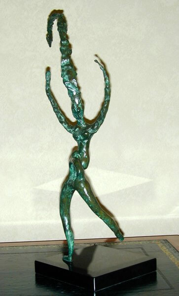 The Rites of Spring - a female figure dancing, arms upstretched and an exceptionally tall headdress which has bent over at the top under its own weight. Sculpture in Bronze.