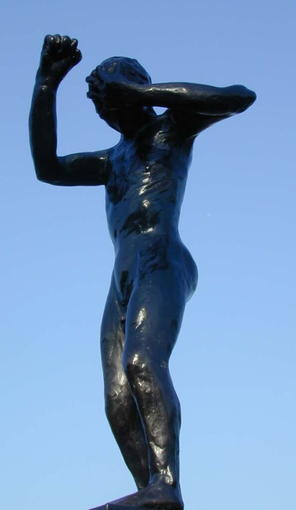 This colour photo shows a fine art bronze sculpture called Speak to us of Crime and Punishment. It is a an adult human with a male physique standing. He is cowering in shame. His head is bent forward so that his chin is almost touching his chest. His left arm is raised horizontally with his left hand covering his forehead. Both legs are slightly bent at the knee. The right hand and arm areup and bent in a defensive, punching posture. He is standing on a highly-polished stone plinth which we can only just see at the bottom of the picture. We are looking at the sculpture's front left side and he is therefore facing left. The background is a completely clear, electric blue sky. The bronze is highly polished and extremely dark in colour.