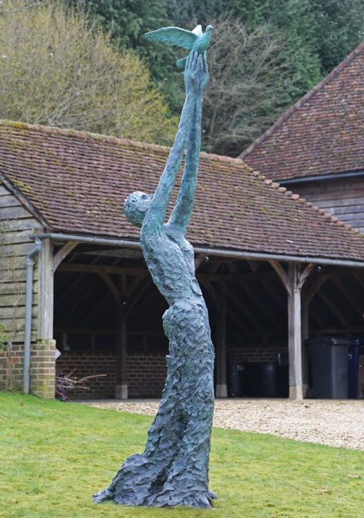 Speak to us of Freedom - Bronze sculpture of a tall slim lady with very long arms aloft, holding up a dove of peace and about to set it free