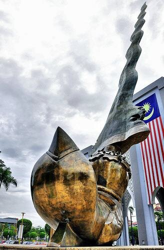 Bronze dagger sculpture with gold handle from the ground. Arches behind, with large Malaysian flag above. Sunny with clouds.
