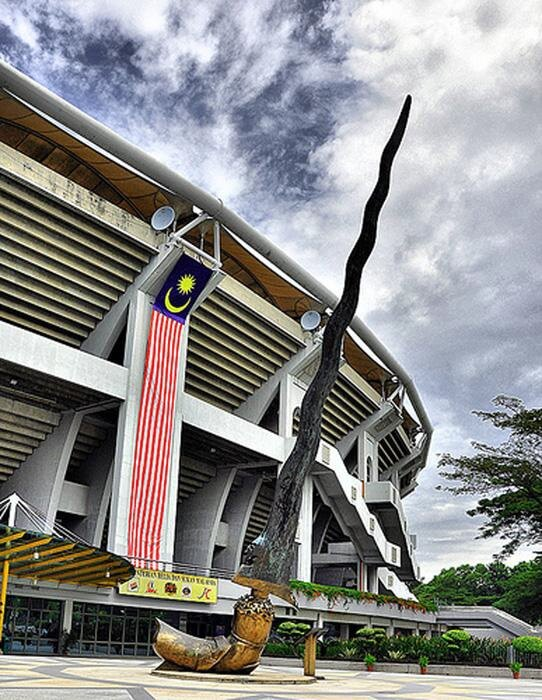 Bronze dagger sculpture with gold handle. Stadium behind, draped in a huge Malaysian flag pennant. Sunny.