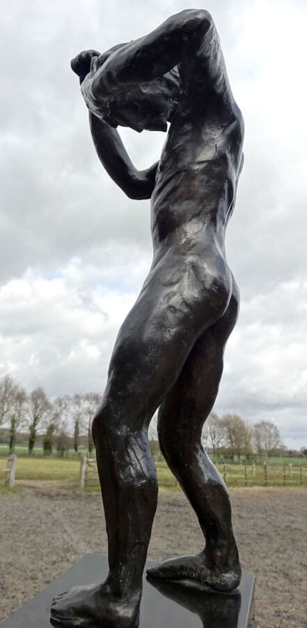 This colour photo shows a fine art bronze sculpture called Speak to us of Crime and Punishment. It is a an adult human with a male physique standing. He is cowering in shame. His head is bent forward so that his chin is almost touching his chest. His left arm is raised horizontally with his left hand covering his forehead. Both legs are slightly bent at the knee. The right hand and arm areup and bent in a defensive, punching posture. He is standing on a highly-polished stone plinth in a brown field. In the middle distance is a wooden post and rail fence with an open gateway to the left of the sculpture. The field beyond has aging grass in it and its boundary is another wooden post and rail fence with immediately behind a row of leafless tall trees, several with ivy climbing the trunks. There are hills in the far distance and the sky is almost completely full of fluffy pal grey and white clouds. We are looking at the sculpture's left side and he is therefore facing left.