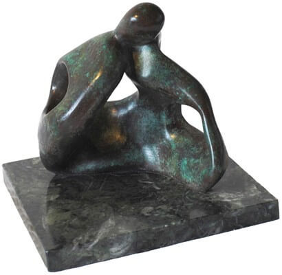 Abstract bronze sculpture of couple sitting on the ground kissing.