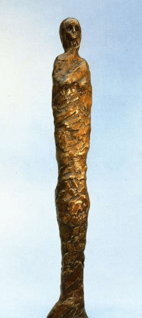 A tall, thin bronze sculpture of a standing woman wrapped in a shroud, with only her face showing. Soft dark gold patina.
