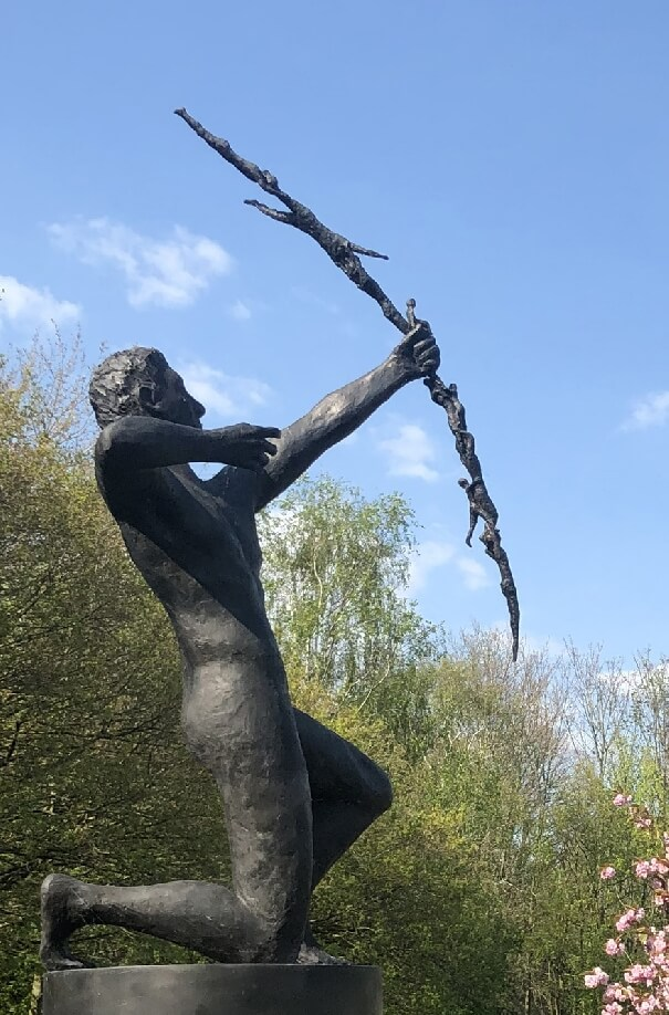 This is a photo of a large, life size bronze sculpture of an androgenous naked man kneeling on his right knee. He is a right-handed archer and he has just fired. His right hand is drawn back, but his fingers are relaxed. His longbow seems to be made of tiny human bodies. He is clearly up high as the photo is taken from below with trees in leaf behind him. There's part of a cherry tree in full pink blossom bottom right. There is a blue sky and quite bright sunshine from left to right. It is based on a sketch by Kahlil Gibran and associated with Speak to us of Children.