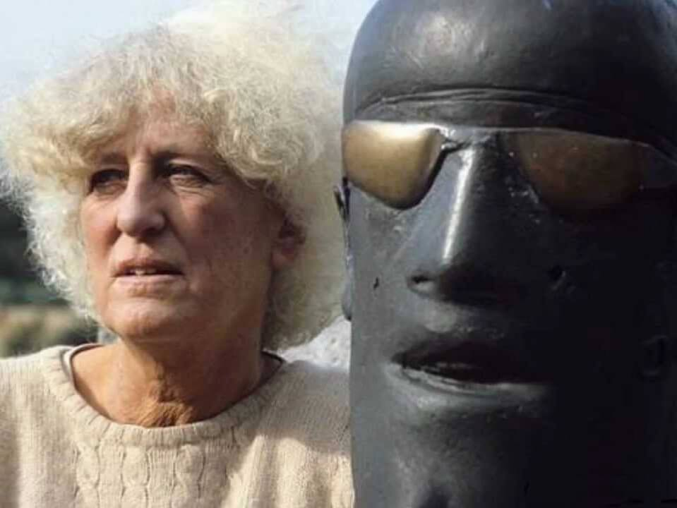 A colour photo of Dame Elisabeth Frink with one of her Goggleheads