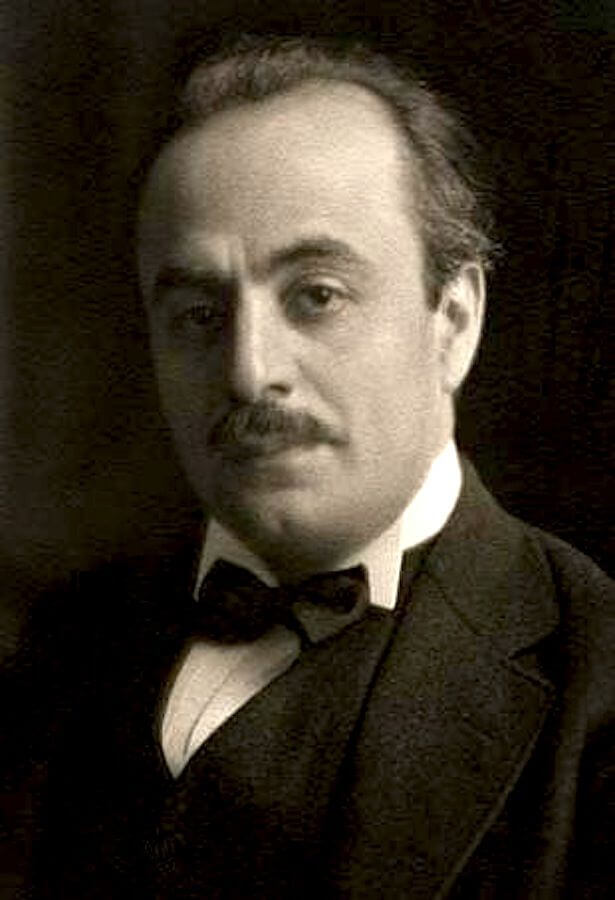 A portrait photograph in black-and-white of Kahlil Gibran wearing a waistcoat, a wing collar and a very dark bow tie. His dark hair is receding and he has a moustache.