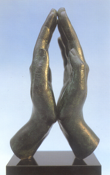 This is a colour photo of a fine art bronze sculpture of two hands joined in prayer. They are adult human hands placed palm-to-palm. The heels of the hands are touching lightly and so are the tips of the longest fingers. Each hand is slightly bowed, so that the only contact between them is at the top and the bottom. The photo is taken from the thumb side and the background shows through between the hands in an almost-symmetrical arc. The bronze hands are mounted on a highly-polished rectangualr mount which is a very dark brown granite. The patina finish on the hands is a gentle golden colour, similar to slightly tarnished brass.