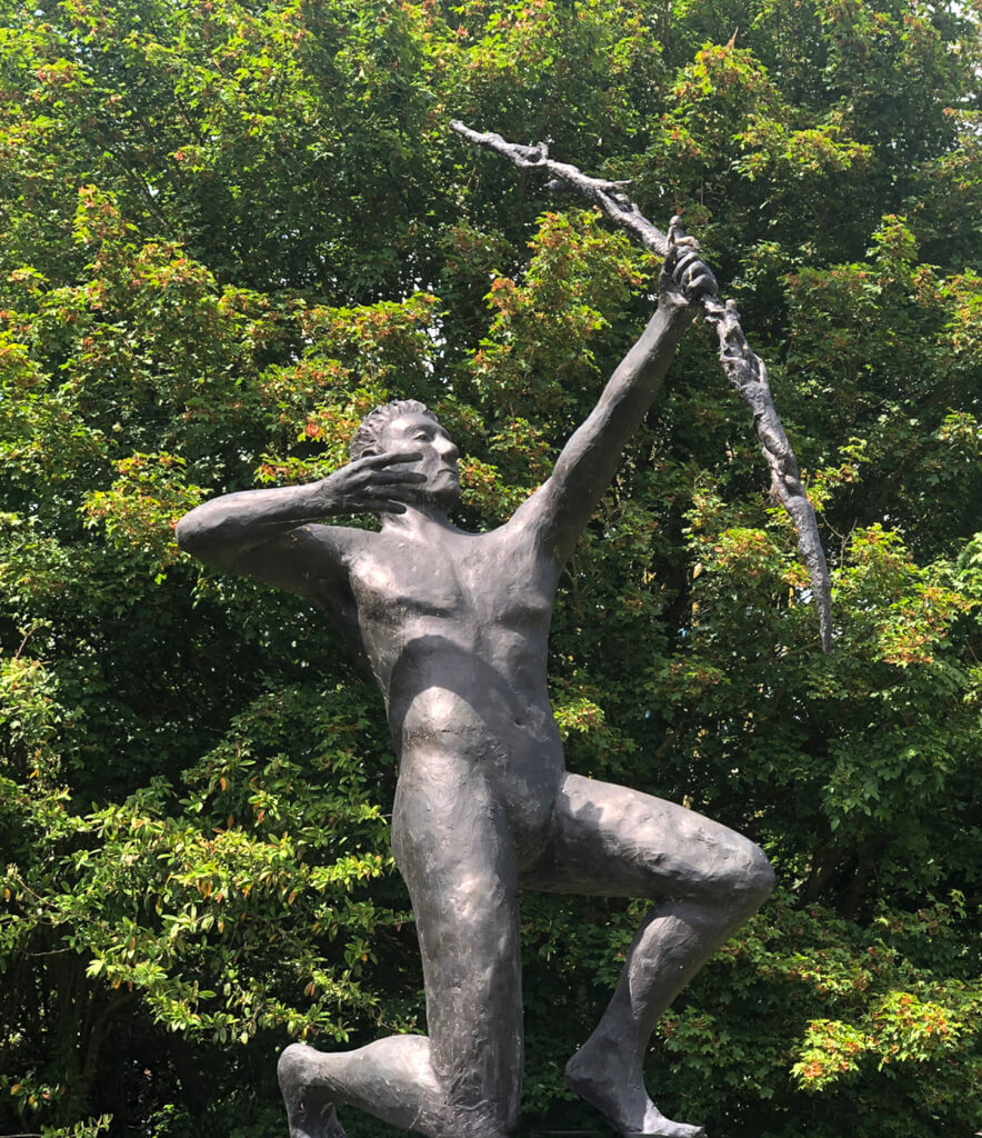 This is a photo of a large, life size bronze sculpture of an androgenous naked man kneeling on his right knee. He is a right-handed archer and he has just fired. His right hand is drawn back, but his fingers are relaxed. His longbow seems to be made of tiny human bodies. He is clearly up high as the photo is taken from below with an oak tree behind him. There is a blue sky and quite bright sunshinine from left to right. It is based on a sketch by Kahlil Gibran and associated with Speak to us of Children.