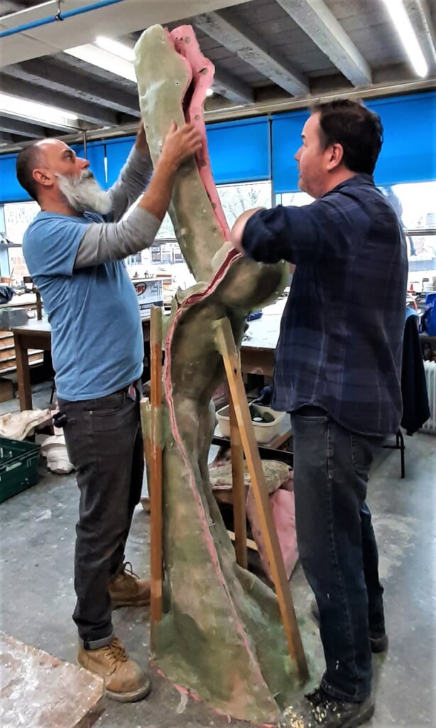Two men facing each other in a workshop. Between them is a mould made from the clay model enlarged from the original. The mould is made in sections and the men are dismantling it ready for the next part of the process.