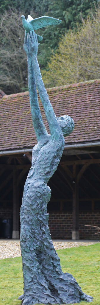 A exaggeratedly tall standing female figure with long skirts. Her arms are held aloft and she is releasing a dove. The bronze statue is standing on a green grass lawn in front of an open barn-type building.