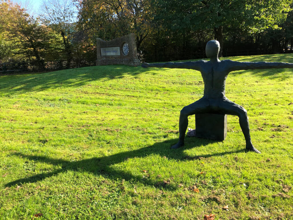A colour photograph of a bronze sculpture, placed on a large piece of grass. There is a row of trees along the back of the photo and the grass and a large brick wall with a wide rectangular stone plaque on the left hand side of the wall which reads 'Chichester College' and a large circular logo on the right hand side of the wall. The sculpture is an androgenous, apparently naked adult human, sitting on a cubewith legs apart at right-angles, thighs horizontal and lower legs vertical. The arms are elongated to roughly twice the natural length and thrust out to each side making a straight line from one hand to the other across the back. The head is heldupright and facing forwards. There is bright, low sunshine streaming from right to left and the shadow of the head, arms and torso forms a perfect cross on the green grass.