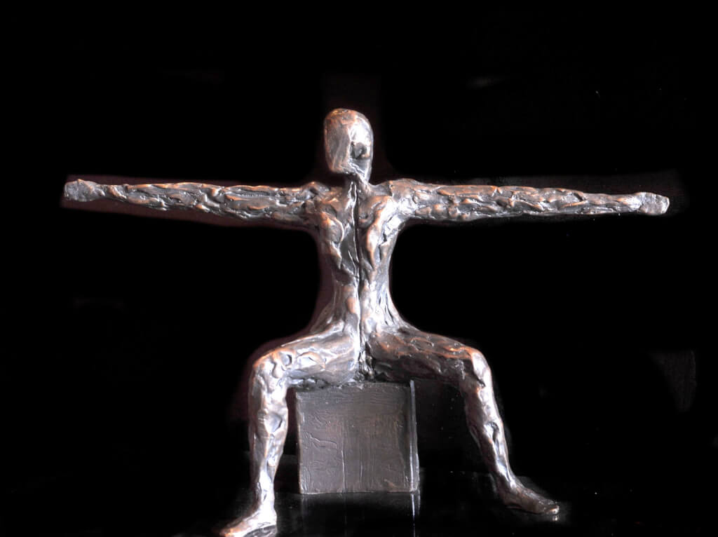 This is a colour photograph of a bronze sculpture, Speak to us of Giving. The sculpture is of an apparently naked androgenous adult human, seated on a cube with legs spread wide at right-angles, thighs parallel to the ground and the feet slightly further from the torso than the knees. The arms are elongated to almost double their natural length and spread wide horizontally so that they form a straight line from hand to hand aacross the back of the torso. The head is upright, but faceless and looking very slightly to its right.