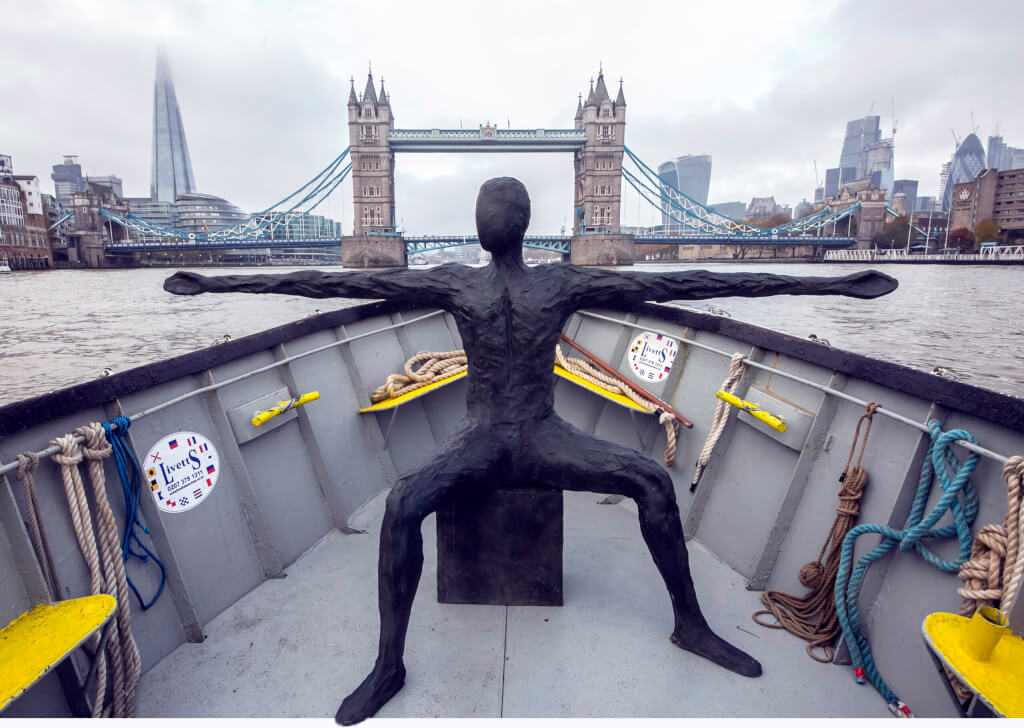 This is a colour photograph of a bronze sculpture, Speak to us of Giving, placed in the bow of a working boat, travelling west along the River Thames in central London. The sculpture is of an apparently naked androgenous adult human, seated on a cube with legs spread wide at right-angles, thighs parallel to the ground and lower legs almost vertical. The arms are elongated to almost double their natural length and spread wide horizontally so that they form a straight line from hand to hand aacross the back of the torso. The head is upright, but faceless and looking very slightly to its right. In the background is Tower Bridge, open to road traffic. The photo is framed so that the head of the sculpture is almost in the middle of the bridge, with the approach roads either sideimmediately above the two outstretched arms. The weather is overcast and grey. The City of London's modern buildings are visible beyond the bridge - The Shard and The Cheesegrater on the left, The Gherkin and The Walki-Talkie on the right.