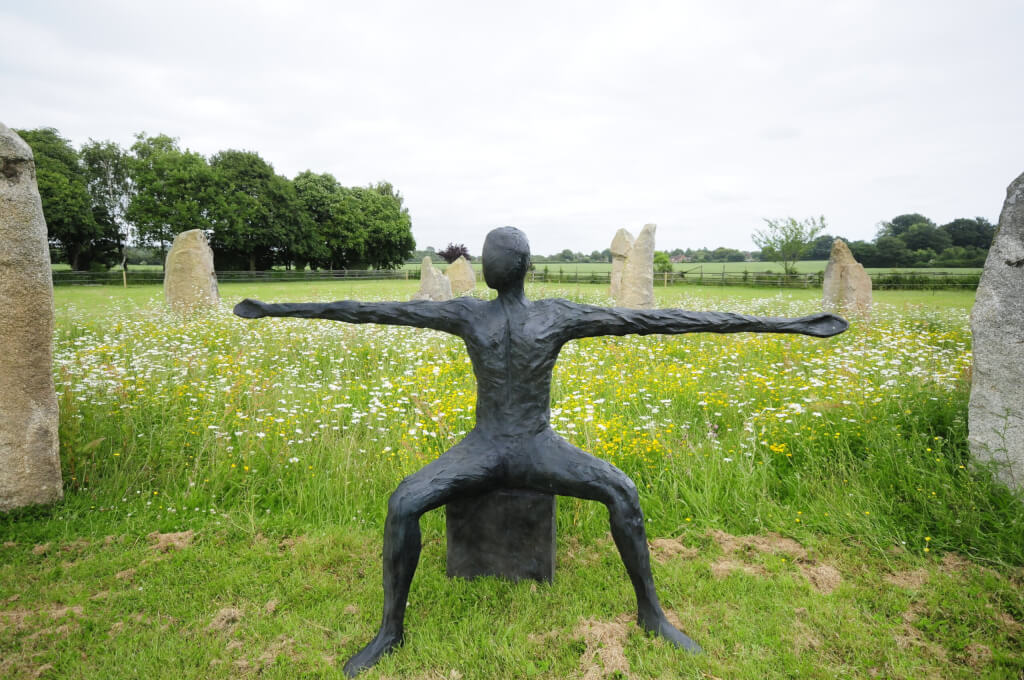 This colour photograph shows a bronze sculpture called Speak to us of Giving, placed on grass in a field. The sculpture is equidistant between two large (~1.8m high) vertical stones which are part of a stone circle and with several of the other stones of the circle visible behind. The sculpture is facing out from the circle. The grass where the sculture is placed has been cut to about 150mm but the grass inside the circle has not and has alarge number of buttercups and daisies growing to about 750mm. The background is the mown field outside the circle with two straight wooden fences, apparently at right-angles meeting at a corner which is obscured but just to the left of centre of the picture. Behind the left hand fence is a row of oak trees of about 20 -30 year old. The sculpture is of an apparently naked androgenous human adult, seated on a cube. The legs are spread wide at right-angles and sloping down slightly. The lower legs are spread out slightly away from the knees. The arms are outstretched and are roughly twice their natural length, horizontal and forming a straight line across the torso. The head is upright and faceless and turned slightly to the figure's right - the left as we look at it.