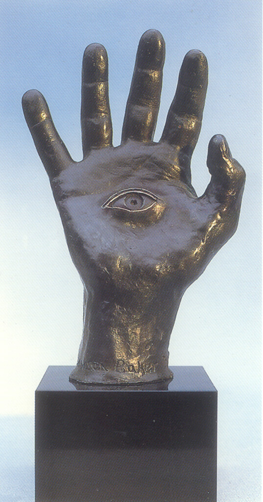 Bronze sculpture of life size human hand. A right hand; palm facing us, fingers up; a central, open, human eye looking out.