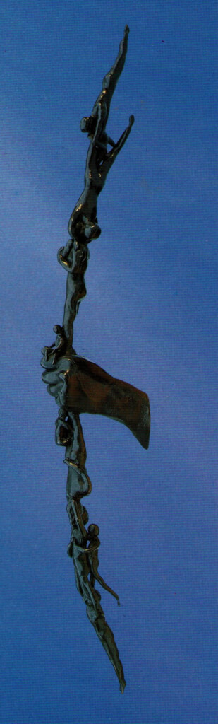 This is a colour photo of a fine art bronze sculpture. It is of a naked left hand holding a longbow vertically and we are looking at the back of the hand. The bow has no string. It is not a conventional wooden bow, but it is formed exclusively of many small, apparently naked, human bodies, possibly children. It is a 3D interpretation of the drawing by Kahlil Gibran for the chapter entitled 'Children' from his book The Prophet.
