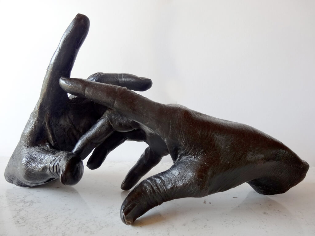 The Sculptor's Hand at work - bronze sculpture of a right hand holding a dentist's drill on a cable