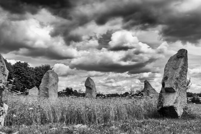 This black & white photo is taken at ground level. It shows six standing stones in a field. The stones seem to form a cluster. The grass in the field has been cut short outside the cluster, but left uncut in the centre of the cluster. There is a very heavy, atmospheric sky, full of clouds of strongly contrasting whites and greys. The tree-lined horizon is just visible behind most of the stones, but the left most ones have oak trees in full leaf close by behind them.