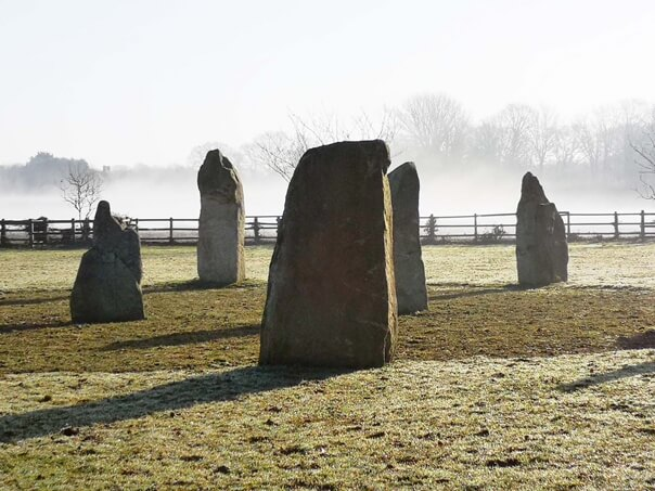 The Sussex Stone Circle. Five Standing Stones. Part of a circle. 3 on the edge and 2 in centre. Fence behind low mist beyond.