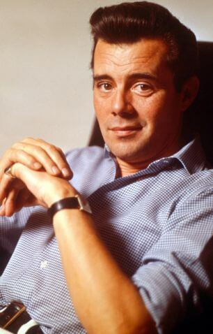 This is a colour photo of Dirk Bogarde sitting in a chair. He is leaning backwards quite far, with both elbows resting on the arms of the chair and his hands meeting in a form of arch in front of him. His right hand is over the top of his left, which has a gold signet ring on his little finger. He is wearing a square wristwatch with a black leather strap. He is lightly tanned. He is looking straight at the lens and has a half-smile. He has very dark hair and eyebrows and dark brown eyes.