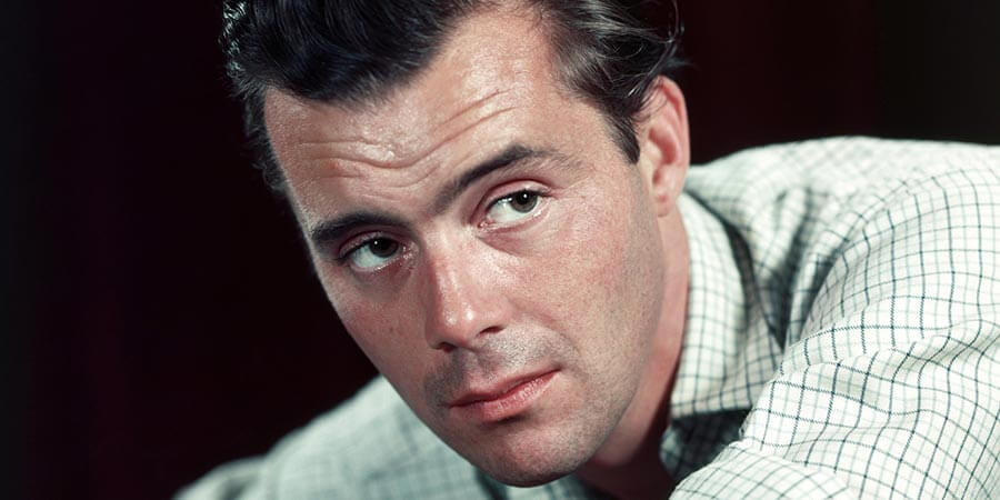 This is a colour photograph of Dirk Bogarde. It shows his face and left shoulder which are in sharp focus, but his neck and right shoulder are out of focus. His body is leaning forward from right to left and his head is turned to the left towards the camera and slightly beyond. He is wearing a white shirt with a dark blue and pale grey check formed by lines crossing at right-angles. He is clean shaven, with black hair and eyebrows and dark brown eyes.