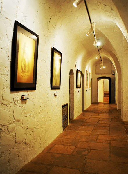 The photo shows a long corridor. It is tall and arched and about 2m wide. The walls are made of stone that has been white-washed and the floor is made of terracotta-coloured stone flags. Five framed pictures hang on the left-hand wall, each with a label or badge underneath it and they are lit by a row of white spotlights which hang from a track suspended from the apex of the arch which runs the full length of the corridor.