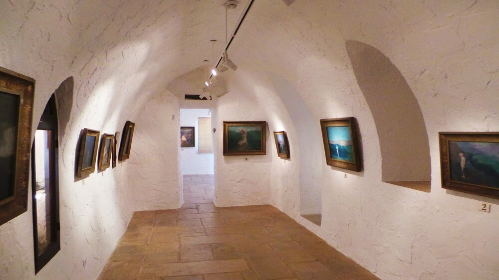 A photo of a stone, white-painted arched gallery within the Gibran museum. Nine paintings hang on the walls illuminated from above by spotlights hanging from a track that runs along the apex of the ceiling arch. Terracotta coloured stone flags are on the floor and there are two doors through to other rooms or galleries.