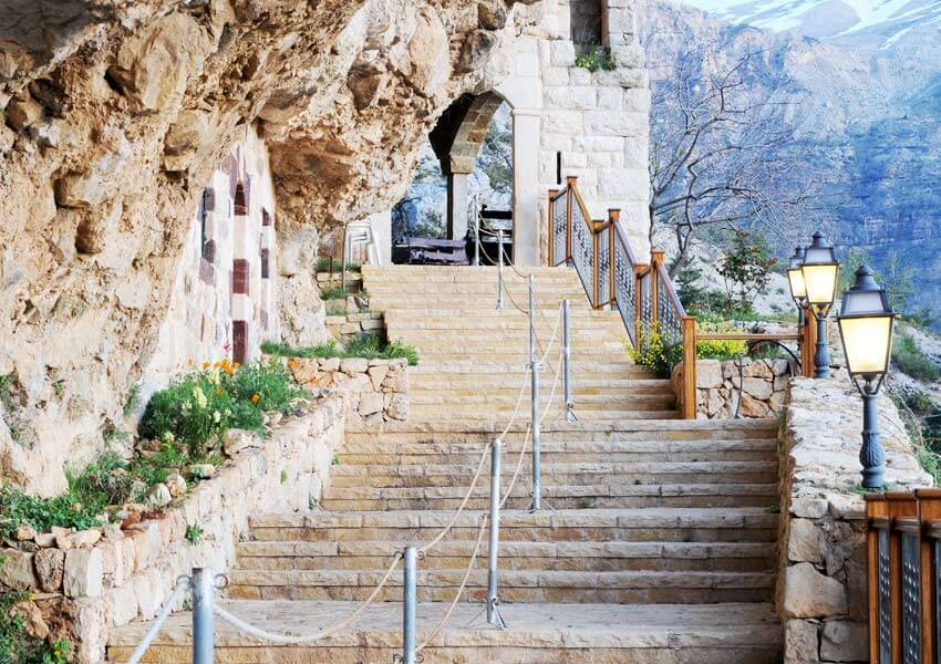 The outdoor stone steps or stairway leading up to the entrance to the former monastery, now museum, with a little snow on the mountains in the background. The arched entrance is at the top of the stairs.