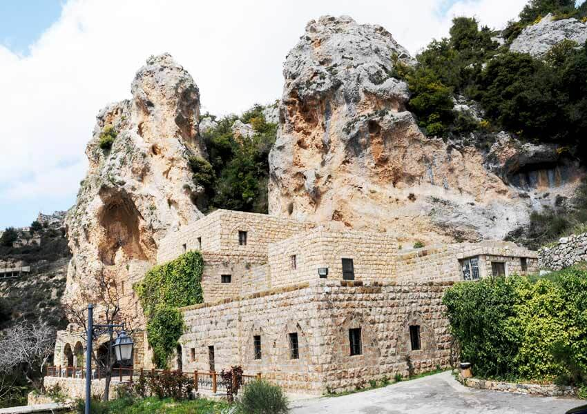 An exterior view of the Gibran Museum. It is a stone-built structure on three floors and very rectangular. There is a series of smallish rectangular windows which have each been formed in the centre of a much larger original monastery arch. Behind and above the building are two colossal pieces of rock, each about the same height as the museum itself. They may once have been a single block with the central 'gap' worn away by the elements. There is a modern lamp post in the left foreground and some tarmac in the right foreground, presumably for parking.