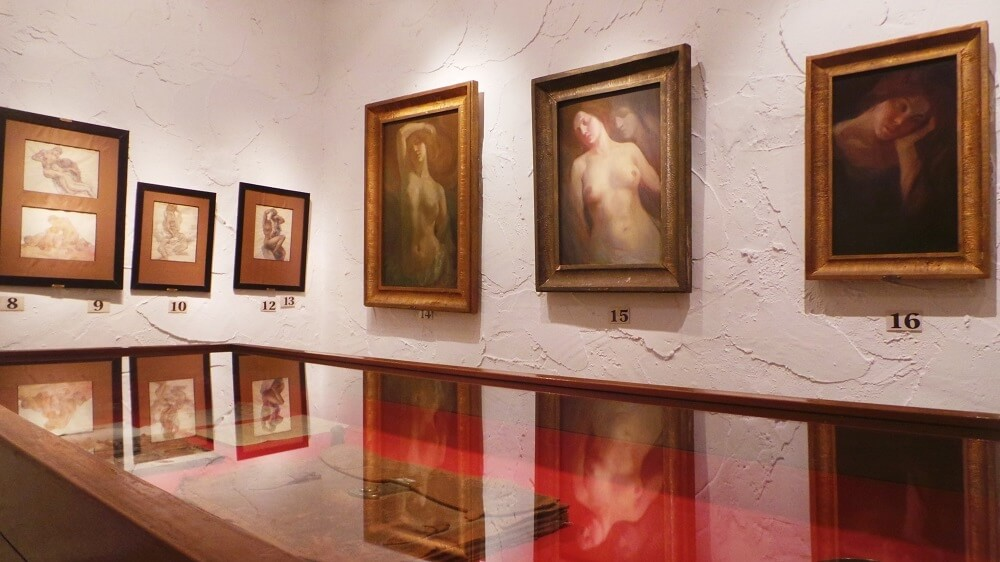 A photo of a gallery room formed of white-washed plastered stone walls and a series of six framed pictures. Three frames hold drawings on paper with mounts and the other three appear to be oil on canvas. The pictures are all reflected on the top of a glass exhibition case containing a briefcase.