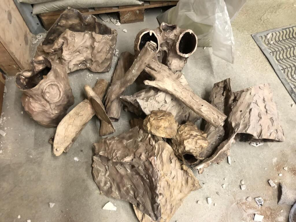 This is a colour photo of some of the individual castings that go to make up the finished bronze sculpture. They are resting on the floor of the workshop in a jumbled pile. Some of the pieces are identifiable such as the hands, the dove, the waist and the upper torso and upper arms, but the rest are incomprehensible!