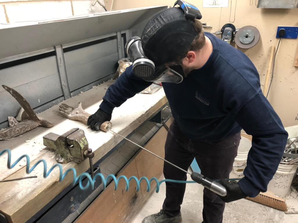 This is a colour photo of the right hand and forearm of the bronze sculpture being cleaned. The casting is resting horizontally and palm up on a workbench in the workshop. A foundryman is standing to the right of the bench facing towards us to the left. He is holding the casting down on the bench with his right hand and using a compressed-air drill with an abrasive tool on a long shaft with his left hand. He is using the tool to remove the moulding clay from the inside of the casting to prepare it for the next stage in the process. The man is wearing a navy sweatshirt, dark jeans and workboots and also a protective helmet with a clear plastic visor and circular breathing filter.
