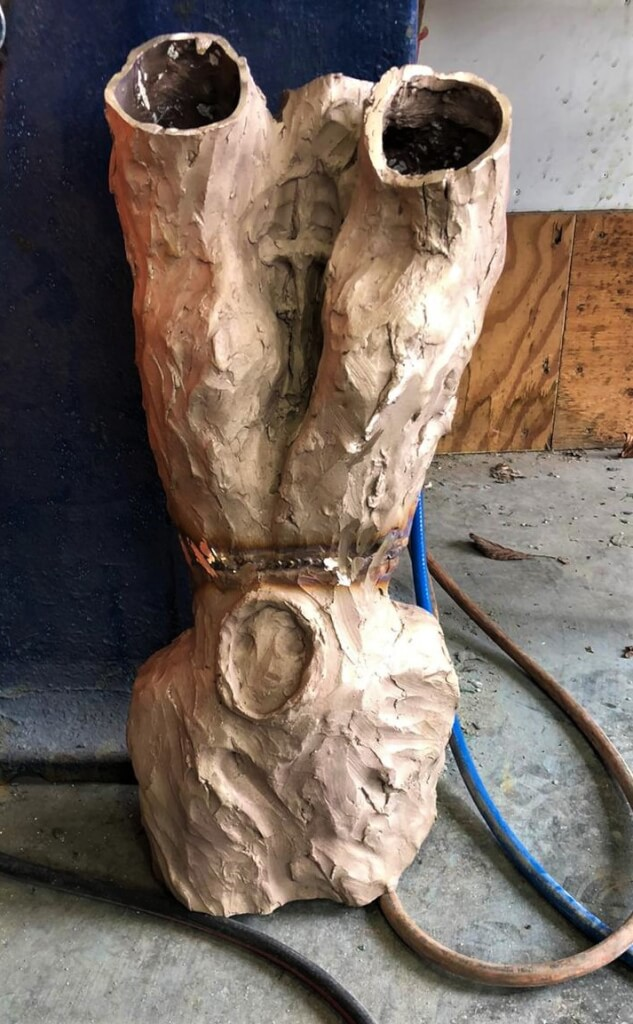 This colour photo shows the mid-section of the sculpture fully assembled and welded. This section is the piece between the bottom of the neck and the very tops of the raised arms down to the bottom of the torso. It is propped up, resting on the floor of the workshop with oxygen, acetylene and argon rubber welding hoses. It is a very pale bronze colour at this stage of the process with a brighter, hooped line where the joint across the waist has been continuously welded.