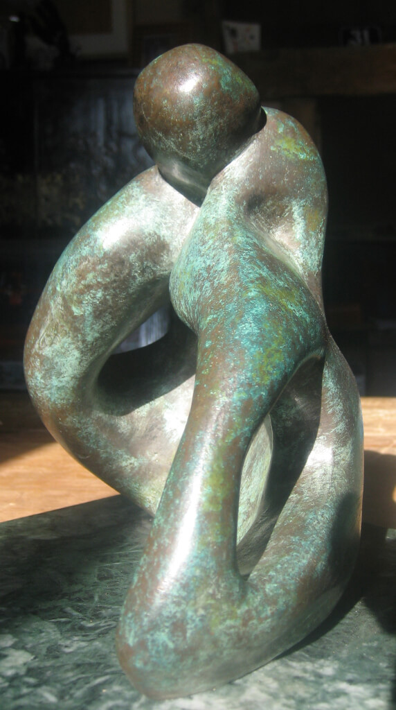 Closeup of abstract bronze sculpture of couple sitting on the ground kissing from the Gibran Sculpture Series. Marble plinth.