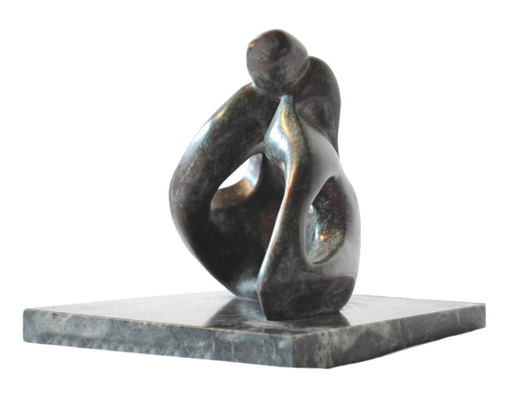 Low view of abstract bronze sculpture of couple sitting on the ground kissing from the Gibran Sculpture Series. Marble plinth.