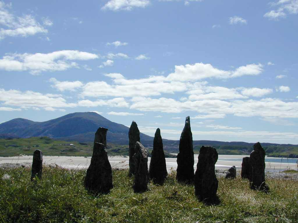 This is a colour photo of standing stones. The stones are a dark grey colour - probably granite and are standing on a grass bank. The other side of the bank is a wide, empty, large, pale, sandy beach which seemes to be the head of an inlet. The calm sea is visible to the right of the stones and behind the right-hand stones. Behind the beach is grass covered land in the distance and low mountains beyond. It is a bright, sunny day. The sun is infront of us but high and out of shot. The sky is a pale, watery blue and there are quite a few fair weather white clouds.