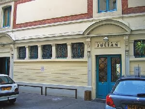 The Academié Julian facade in Paris in 2019. It is a handsome but somewhat understated building. There are double doors with the lower third panelled and the upper two-thirds glazed with pretty, diagonal patterened, black wrought-iron grills over them. The doors themselves are painted blue, almost turquoise. Above the door there is a sign which reads 'JULIAN' in block capitals and above that a wide decorative arch. The walls of the building are painted a cream colourand below the height of the arch and to its left are five square windows separated by pillars with ornate crowns and pedestals. Above the door are two vertical windows which are painted the same colour as the doors below and to the left of these windows, above the square ground-floor windows is a very wide cream panel defined by a thick brick-red border.