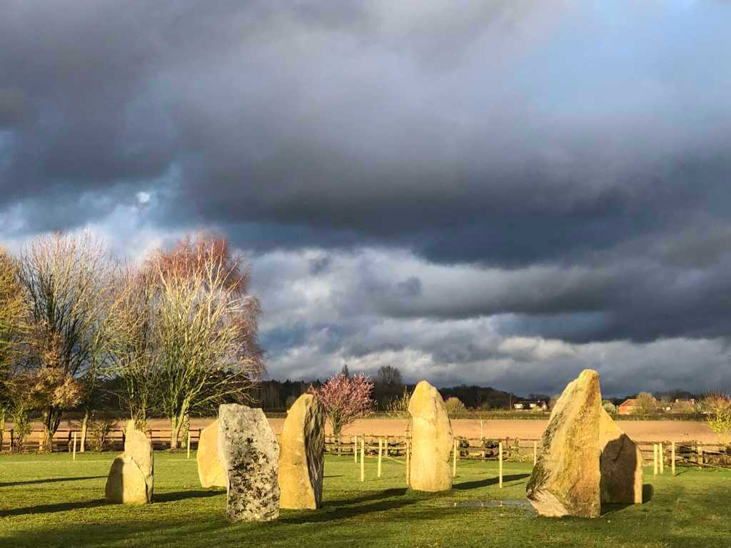 The Sussex Stone Circle. Group of upright 1.5m stones in a mown green grass field, 6 in a circle and one in the centre. Sun.