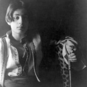 A black and white photograph of a very relaxed, seated Kahlil Gibran. He seems to be wearing clothes typical of the Lebanon of the very early twentieth century.