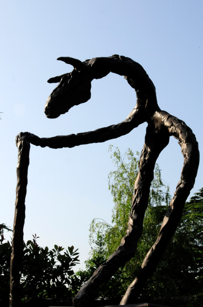 Bronze sculpture. A horse with a long neck, standing vertical on its hind legs, a single front leg holding a walking stick.