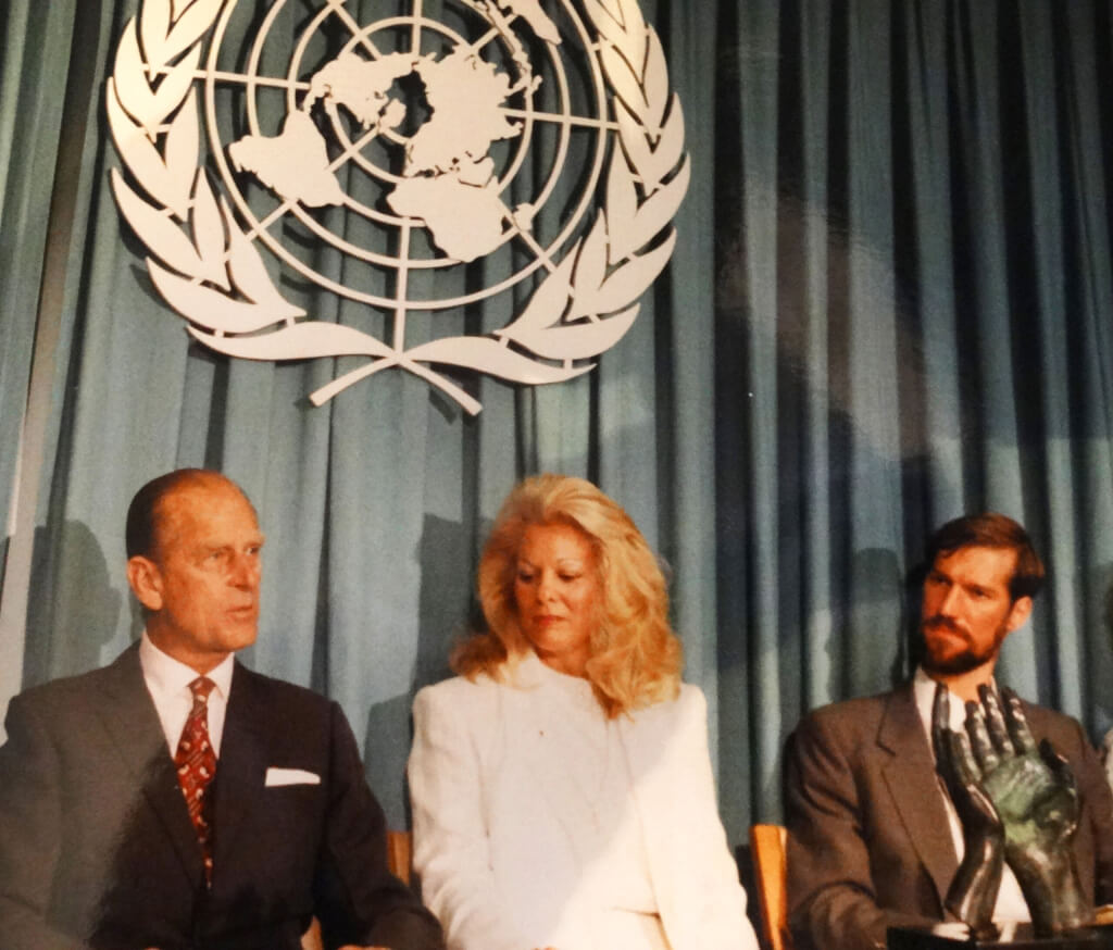 HRH Prince Philip Duke of Edinburgh (left) at the UN in New York to present bronze sculpture Hands in Prayer. UN logo above.
